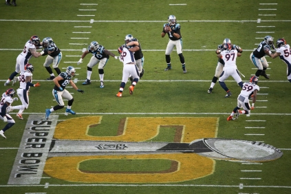 Cam Newton (1) drops back for a pass near the 50-yard line. The large Super 50 logo looms in the foreground