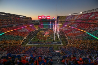 "Coldplay, Beyoncé and Bruno Mars perform during the halftime show while the crowd holds up colorful cards that spell out ""Believe in Love"""