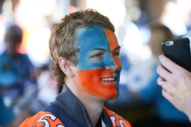 A Broncos fan checks out his face paint prior to the game